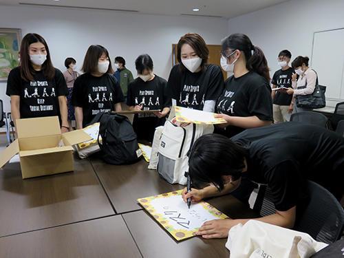 HP記念撮影前にメッセージを書く学生.jpg