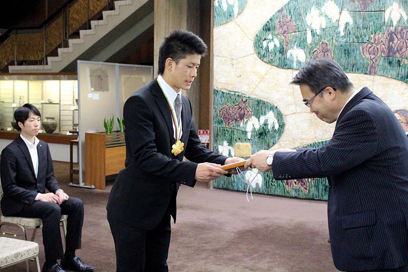 大村知事から顕彰盾を受ける堀島選手(左は船渡コーチ)-a.jpg
