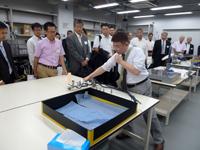 機械加工室の最新設備の説明を聞く参加者