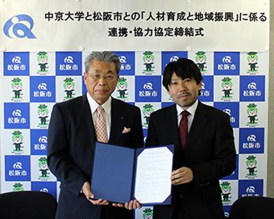 サインした協定書を持つ北川学長(左)と山中市長